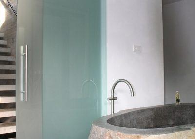 Natuurstenen ligbad en glazen schuifdeur